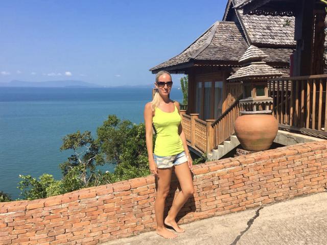 Frau vor Poolvilla mit Blick auf Meer