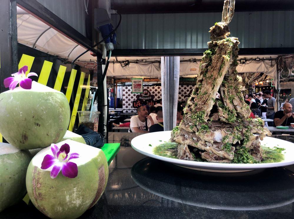 Tisch mit Kokosnüssen und Teller mit Fleisch