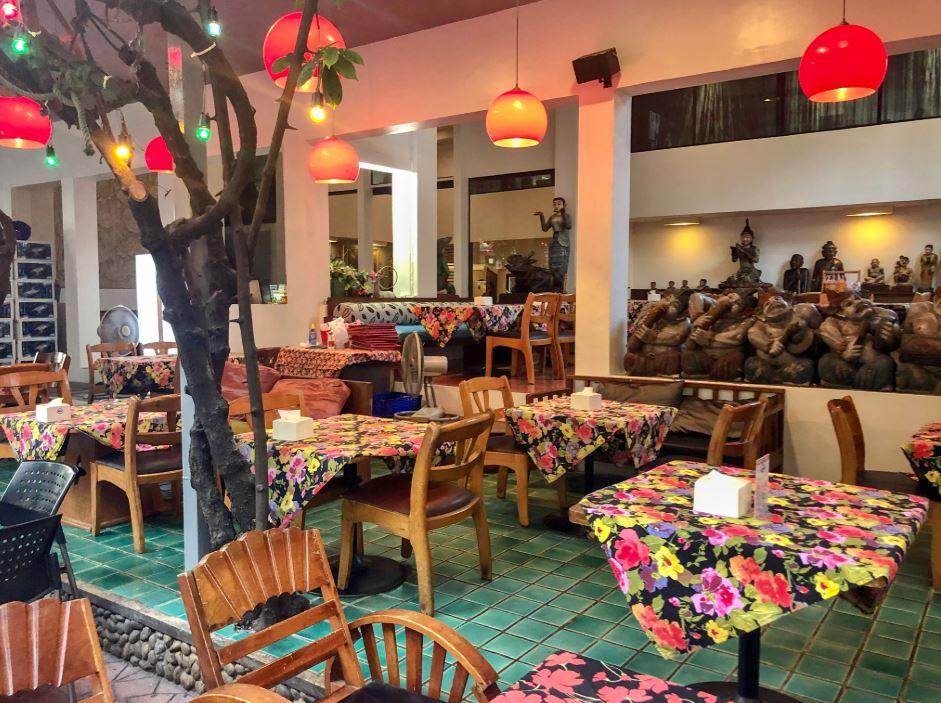 Restaurant mit roten Lampen und bunten Tischdecken