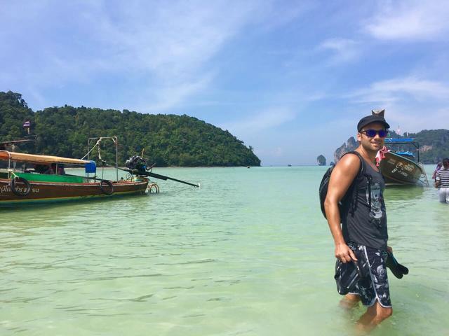 Mann im Wasser vor Boot auf Phi Phi Don Thailand