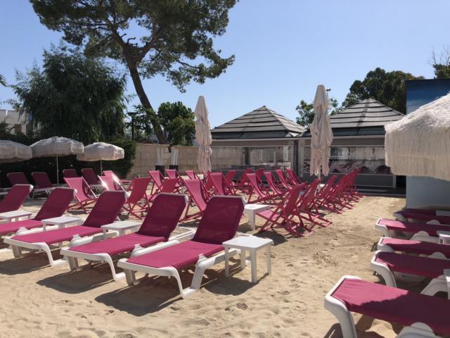Liegestühle im Sand vor Hotel