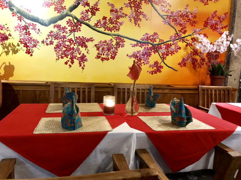Restaurant mit roten Tischdecken und Blumen an der Wand