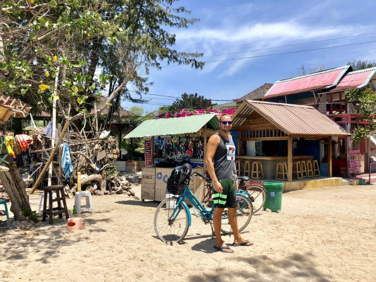 Mann vor Fahrrad am Strand