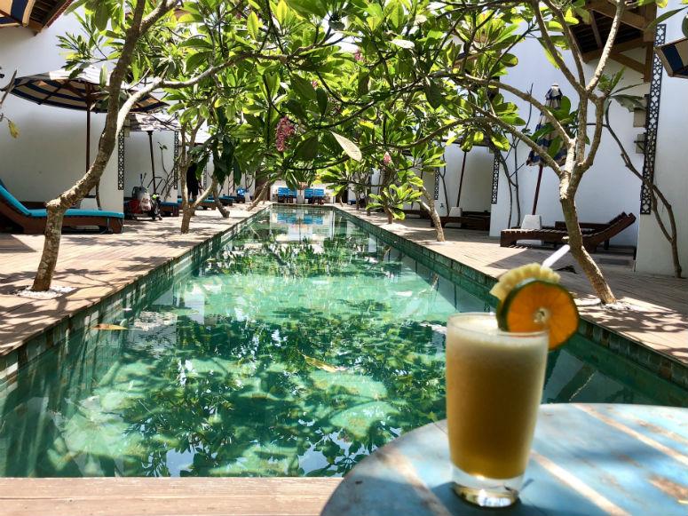 Getränk auf Tisch vor Pool