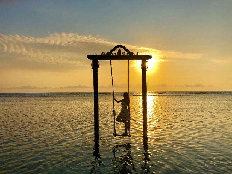 Frau auf Schaukel in Meer