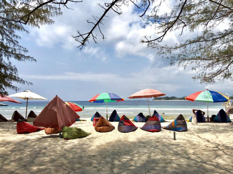 Strand mit bunten Schirmen und Sitzsäcken auf Gili Trawangan