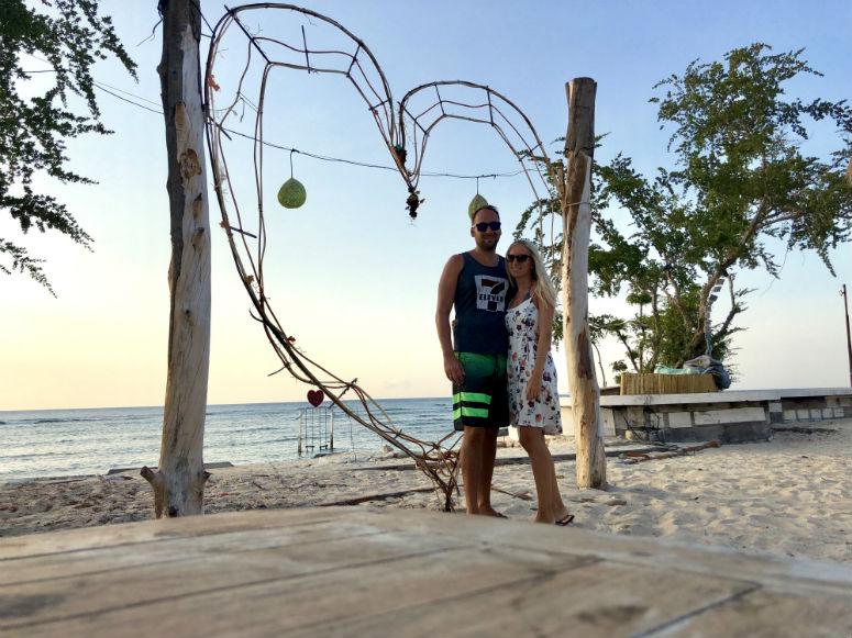 Pärchen steht vor großem Herz am Strand