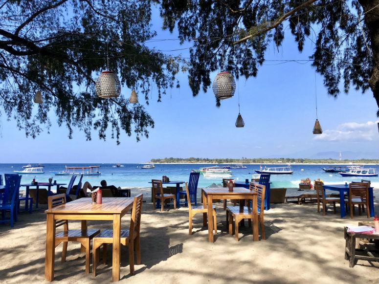 Tische und Stühle am Strand mit Sicht auf Meer
