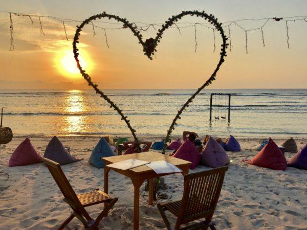 Tisch am Strand auf Gilitrawangan bei Sonnenuntergang mit großem Deko-Herz