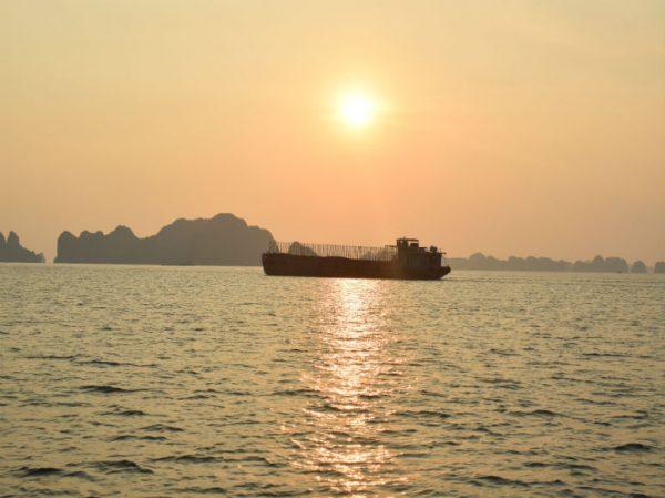 Meer Halong Bucht mit Schiff, Bergen und Sonne im Hintergrund