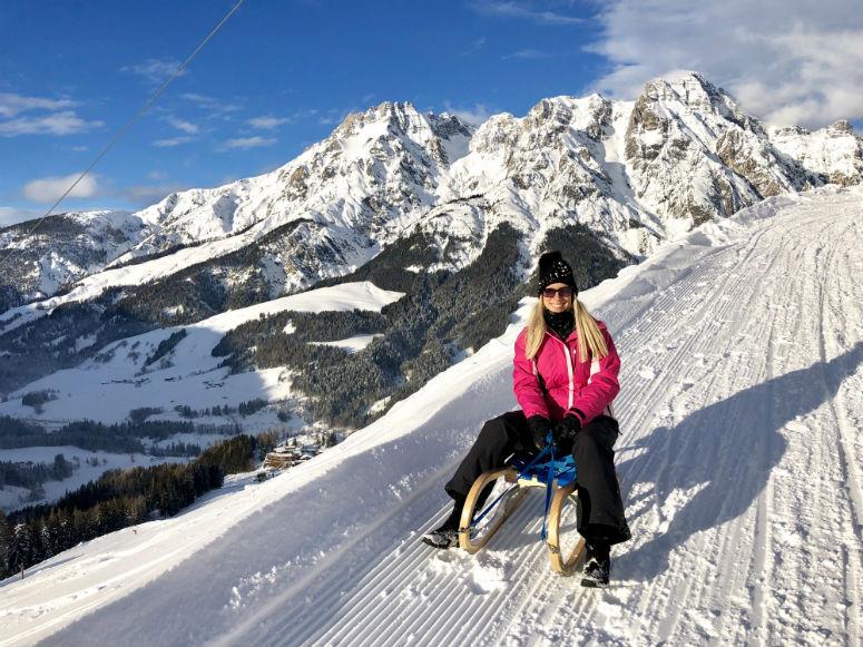Frau auf Schlitten vor Bergpanorama
