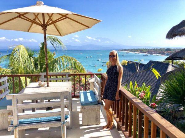 Reiseblogs, Frau auf Balkon mit Meerblick