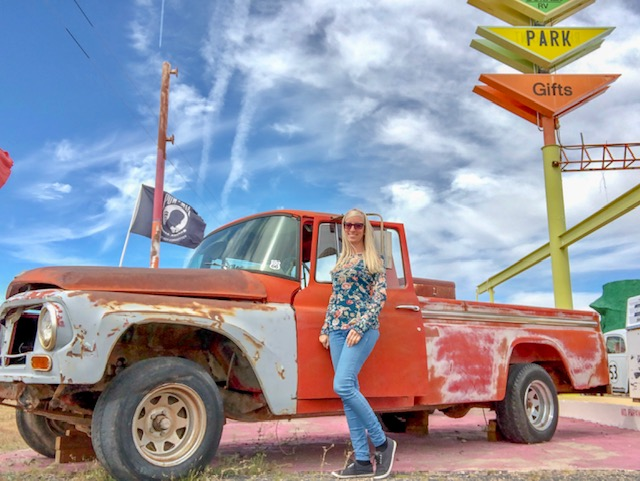 Frau vor altem Auto an der Westküste USA