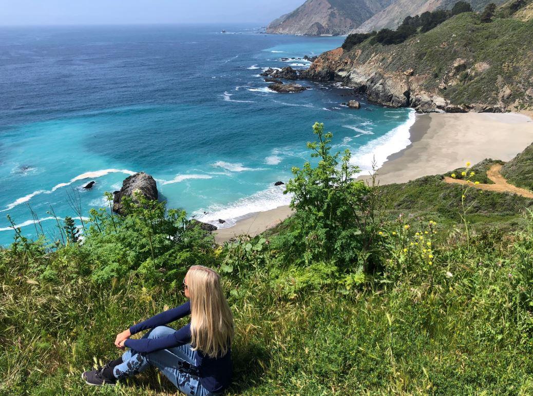 Frau sitzt auf Wiese mit Sicht auf Meer am Highway 1 an der Westküste USA