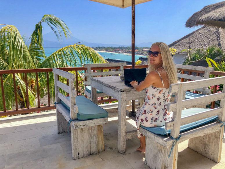 Reisen und arbeiten, Frau mit Laptop und Aussicht über Meer