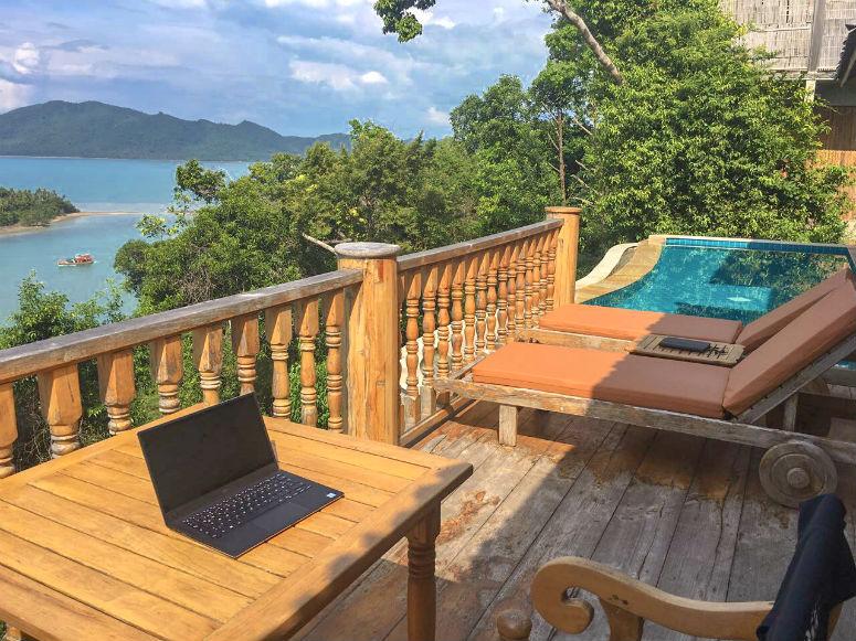 Reisen und arbeiten, Laptop auf Terrasse mit Blick auf Pool und Meer
