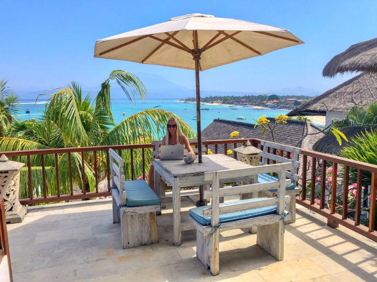 Reisen und arbeiten, Frau sitzt auf Balkon am Laptop mit Sicht auf Meer