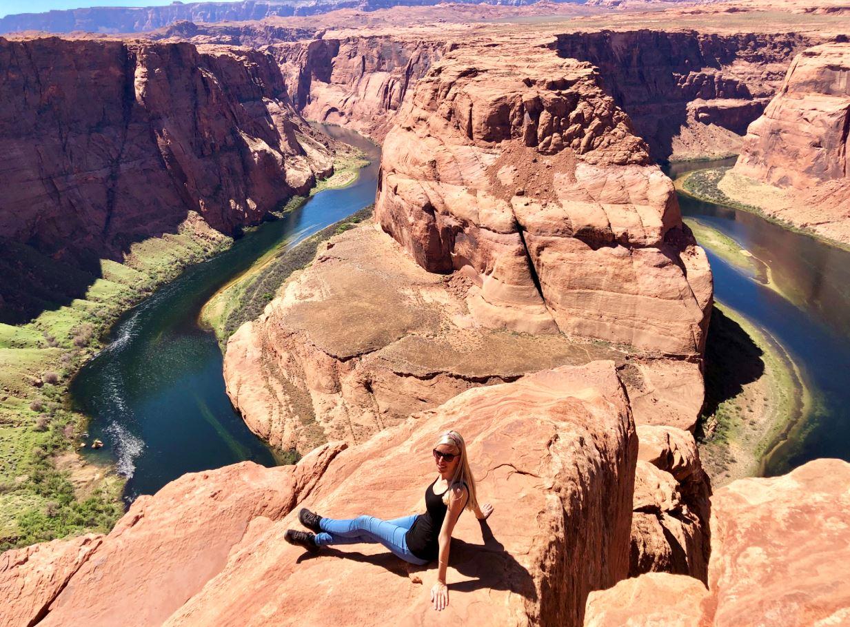 Nationalparks der USA, Frau sitzt vor Horseshoe Bend auf Felsen