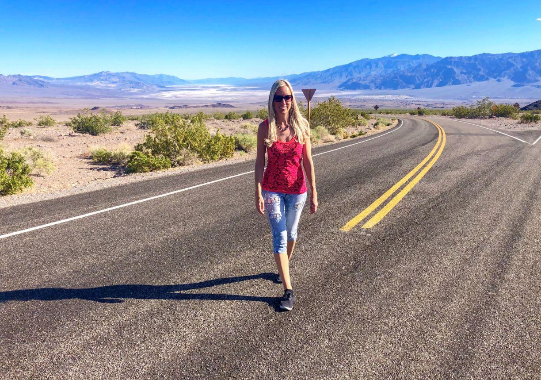 Nationalparks der USA, Frau steht auf Straße imDeath Valley
