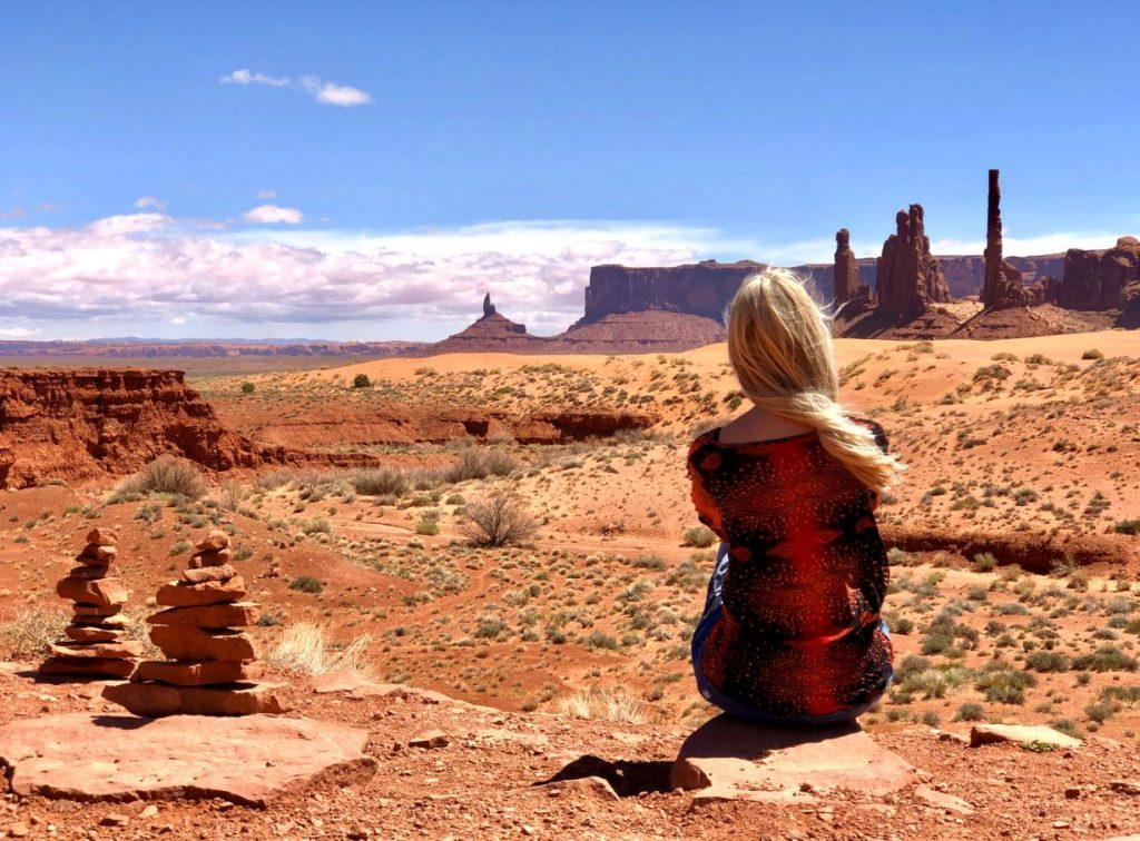 Sehenswürdigkeiten und Nationalparks der USA, Frau sitzt im Monument Valley
