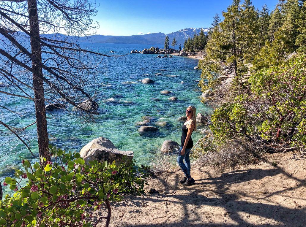 Frau steht am Secret Harbour Beach vor türkisem Wasser