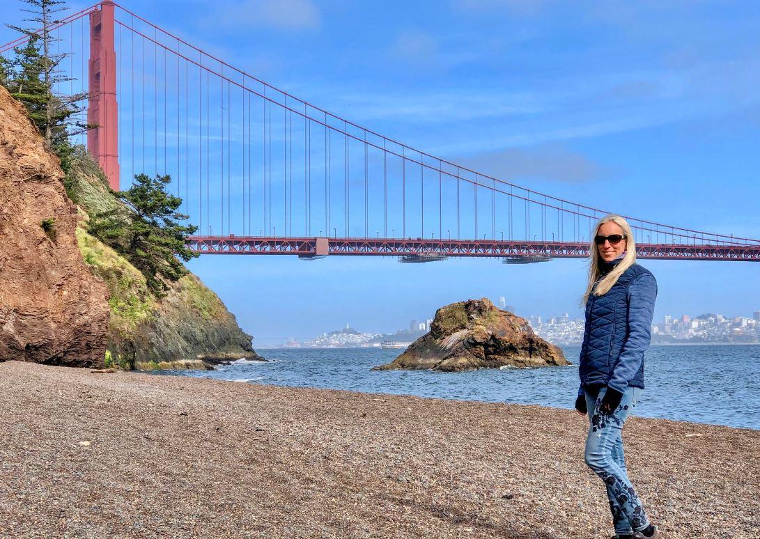 San Francisco Sehenswürdigkeiten, Frau am Strand vor Golden Gate Bridge