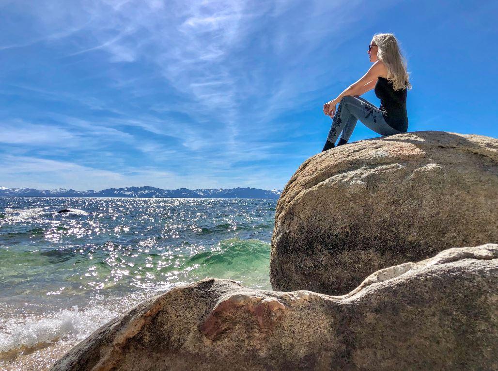 Wissenswertes über den Lake Tahoe, Frau sitzt auf Felsen am See
