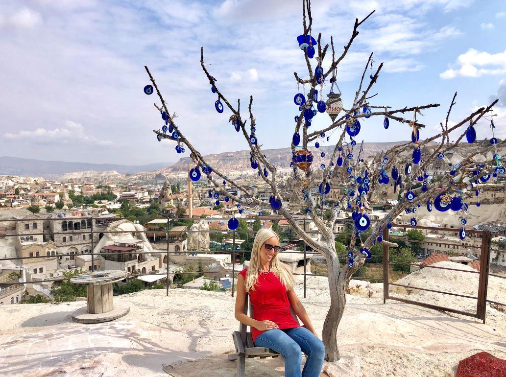 Göreme Kappadokien, Frau sitzt vor Baum mit türkischen Augen