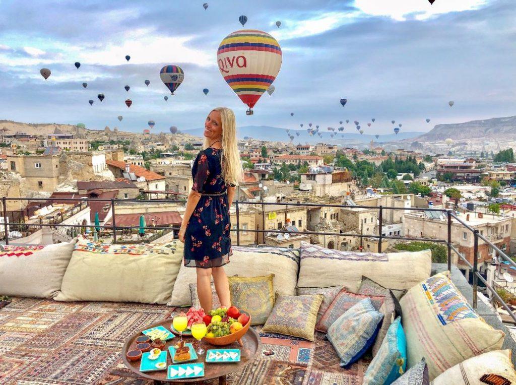 Kappadokien Reise, Frau auf Terrasse mit Ballons am Himmel