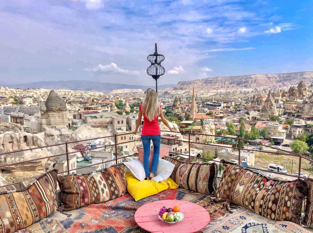 Kappadokien Sehenswürdigkeiten, Frau auf Terrasse mit bunten Kissen