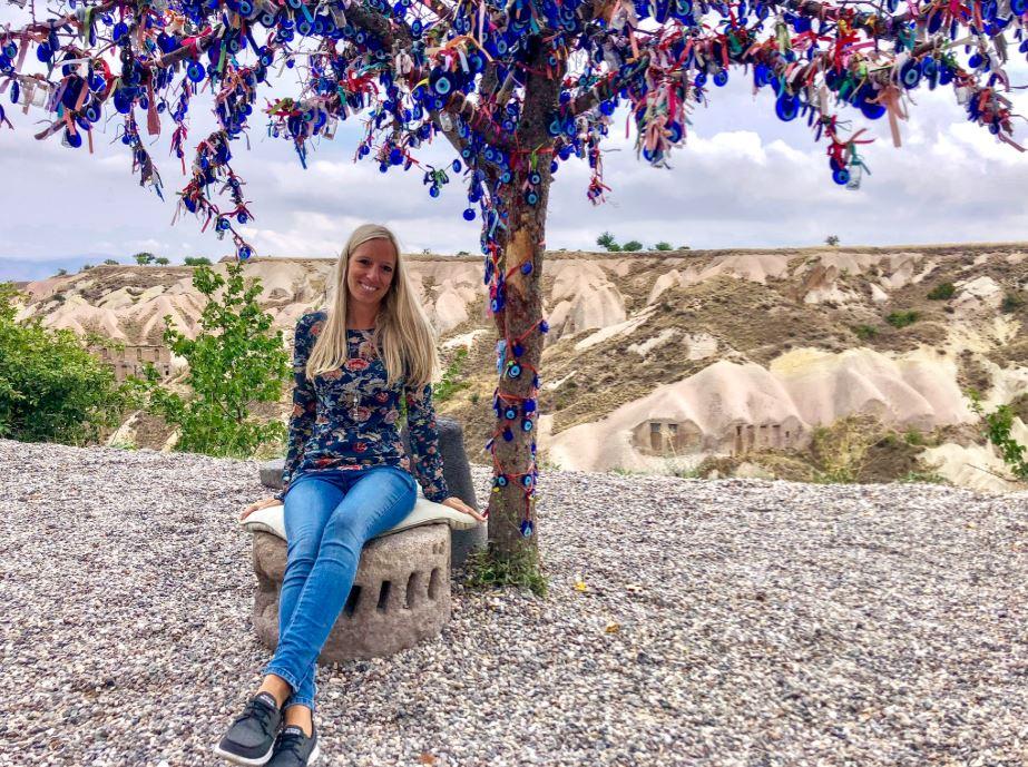 Taubental Kappadokien, Frau sitzt unter Baum mit türkischen Augen