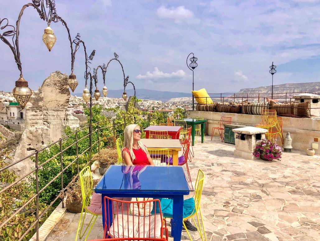 Hotels in Kappadokien, Frau vor bunten Stühlen und Tischen