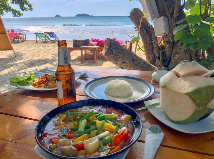 Thai-Curry, Reis, Kokosnuss und Bier auf Tisch mit Meerblick
