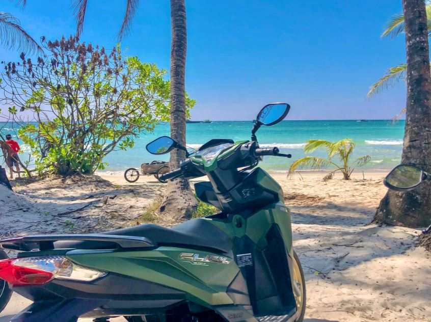 Rollerfahren auf Koh Chang, Roller steht am Strand vor türkisem Meer