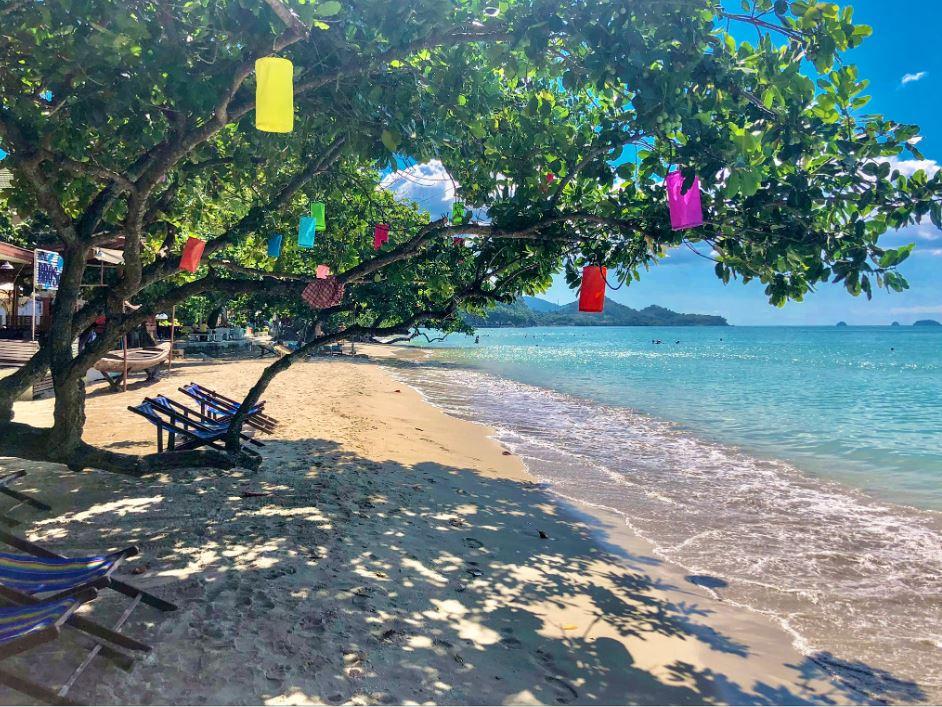 White Sand Beach Koh Chang, weißer Strand mit kleinen Liegestühlen und Lampions im Baum