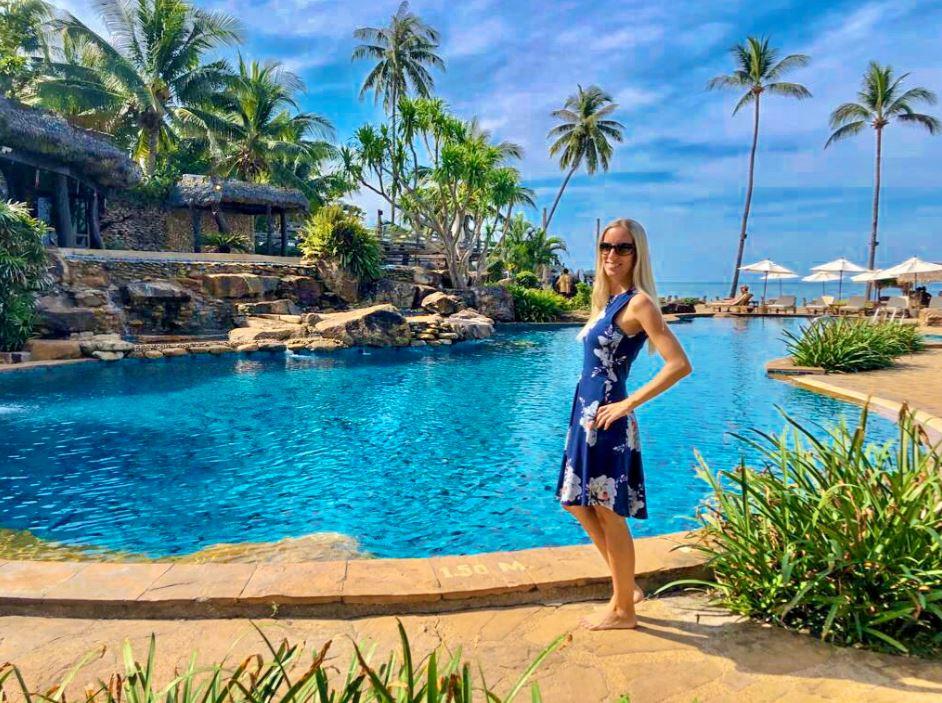 Frau im blauen Kleid steht vor Pool im Santhiya Tree Resort
