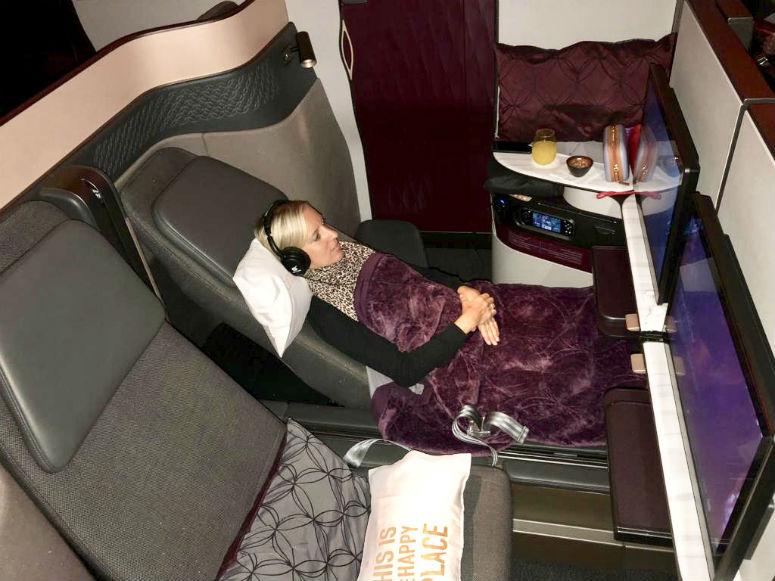 Amex Gold Card, Frau mit Kopfhörer sitzt in großem Abteil der Qatar Airways Business Class