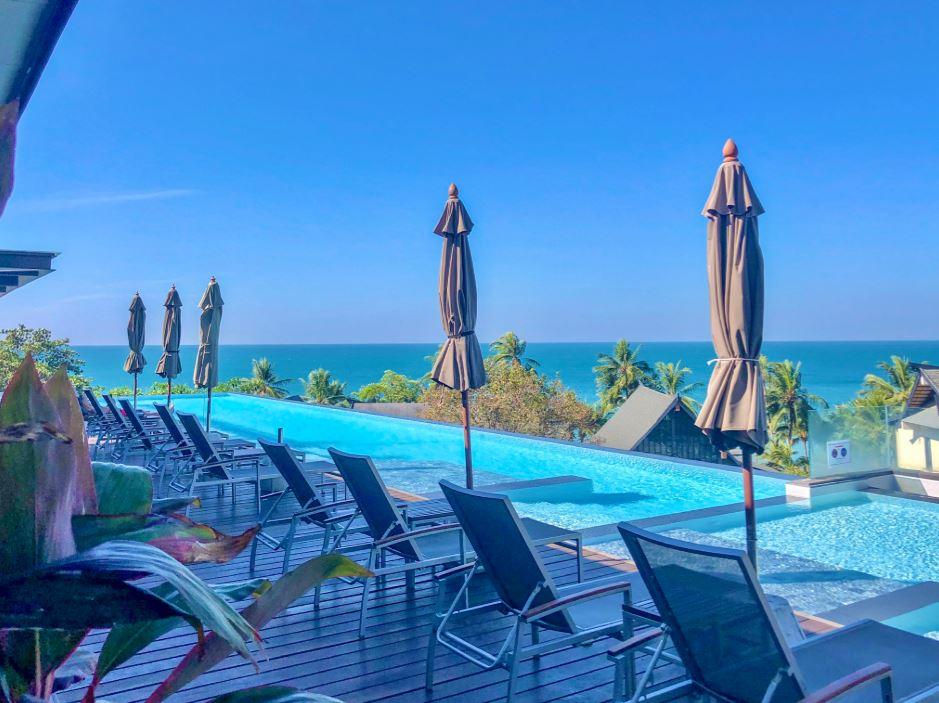 KC Grande Hotel, Infinity Pool mit Liegestühlen, Schirmen und Sicht auf Meer