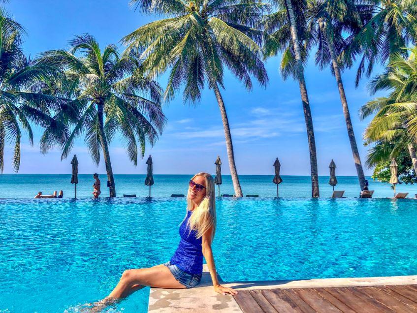 Frau sitzt vor Pool mit Palmen und Meer im Hintergrund