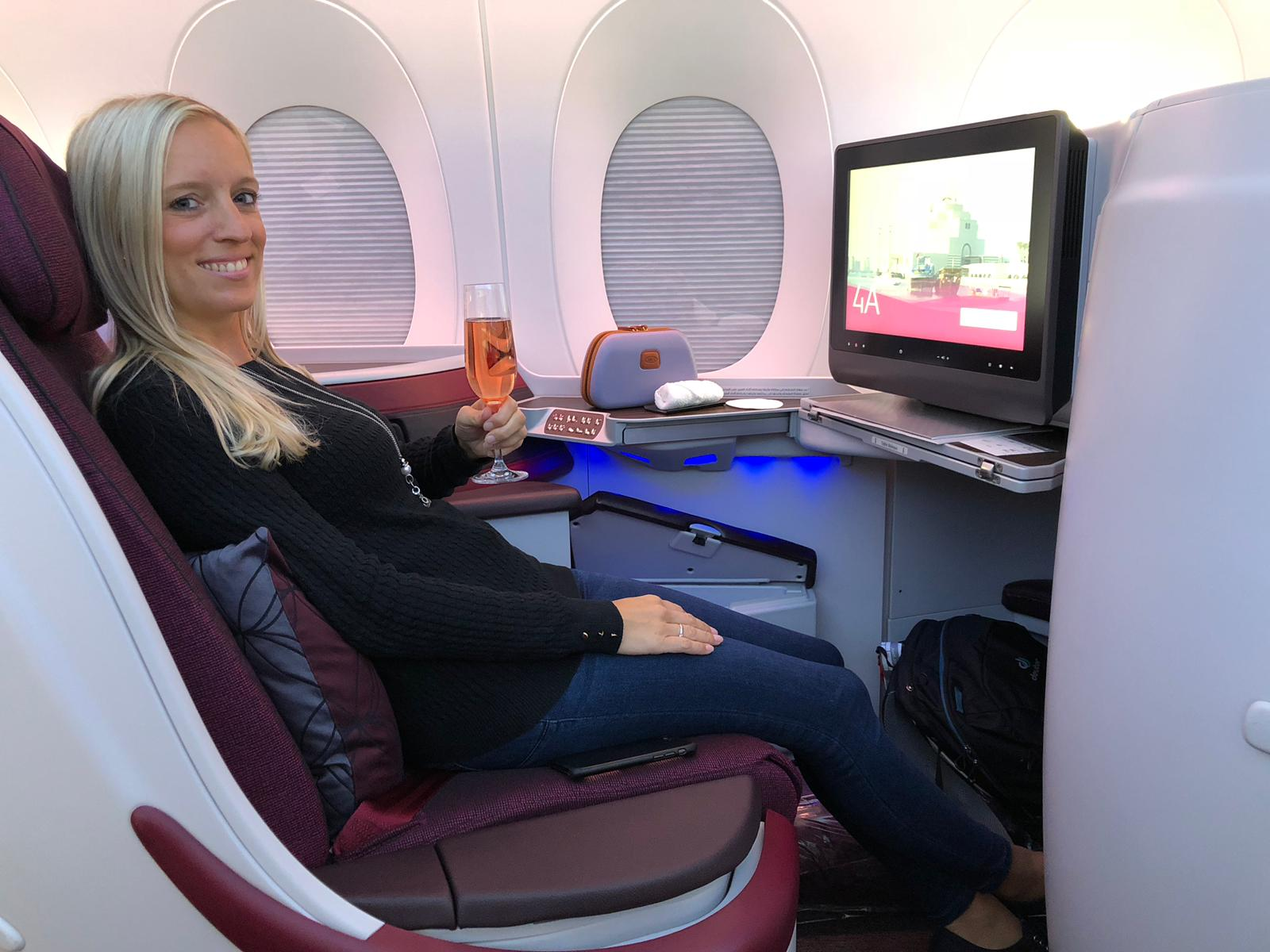 American Express Gold Card, Frau mit Sekt in der Hand sitzt in Business Class