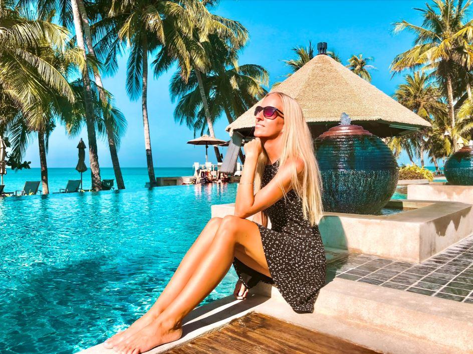 Frau im schwarzen Kleid sitze am Pool mit Meer und Palmen im Hintergrund