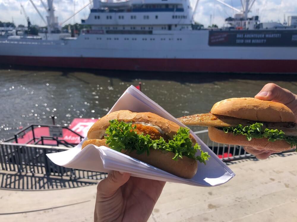 Zwei Fischsemmeln in der Hand mit Blick auf Schiff im Hamburger Hafen