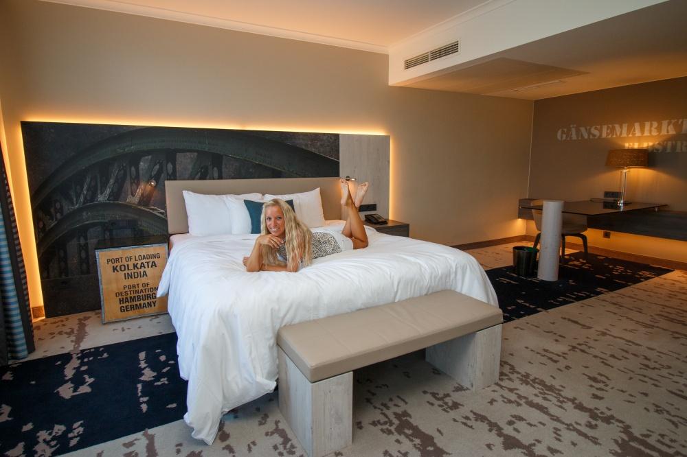 Das Renaissance Hamburg Hotel, Frau liegt auf Bett mit Hand unter dem Kinn