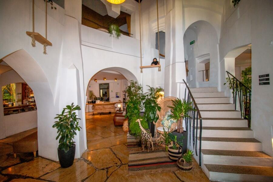 Eingangsbereich der Hotellobby mit grünen Pflanzen und Treppe