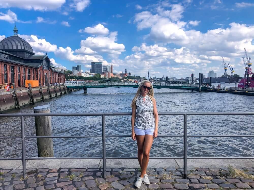 Hamburg Tipps, Frau steht vor Elbe an Zaun in Hamburg