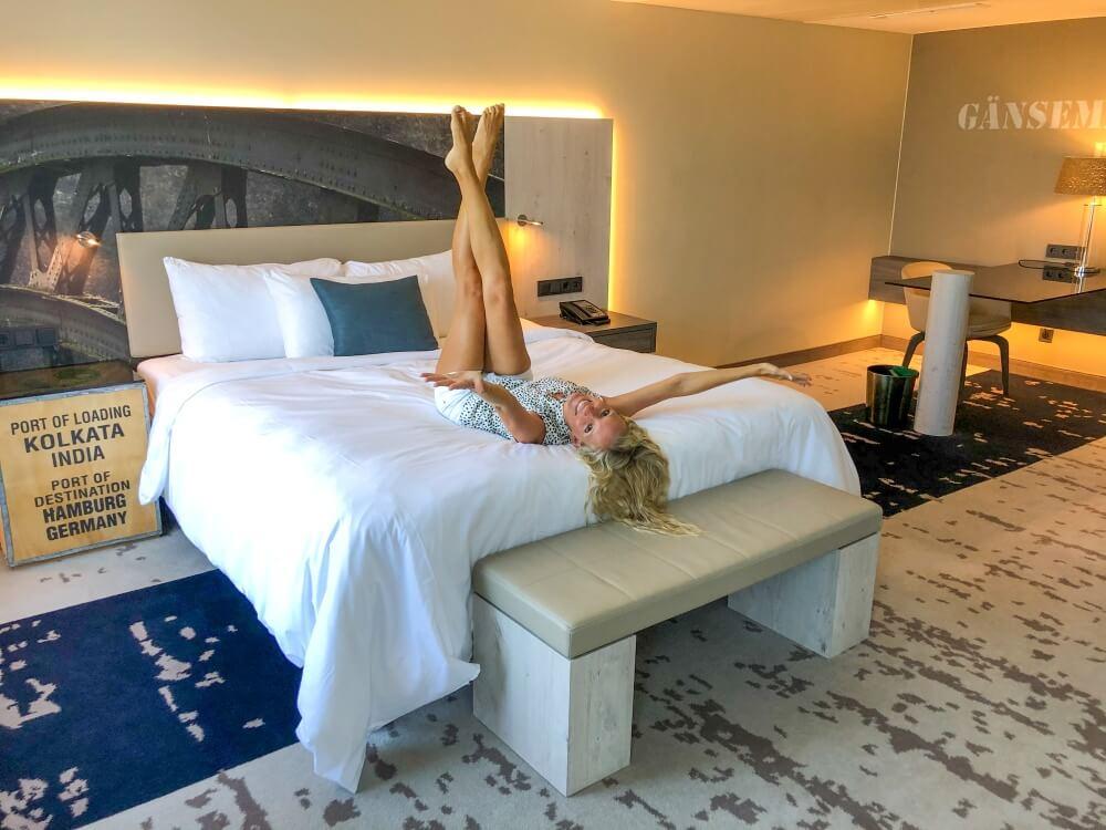Frau mit hochgestreckten Beinen und Armen auf Bett