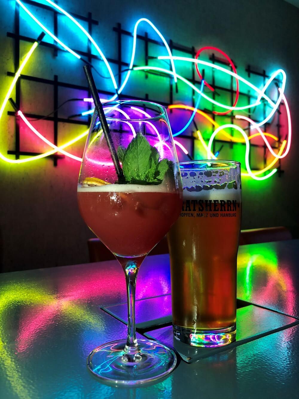Cocktail und Bier vor bunt leuchtender Wand in Hotelbar