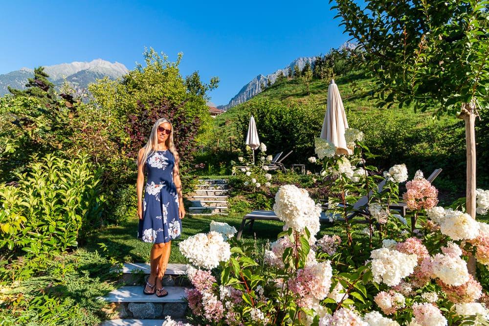 Frau in blauem Kleid steht vor weißen Blumen mit Bergen im Hintergrund