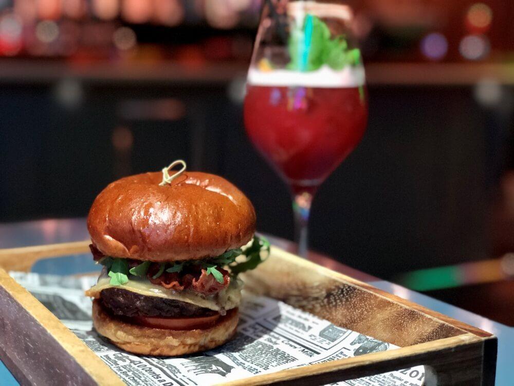 Burger auf Tablett mit Cocktail daneben