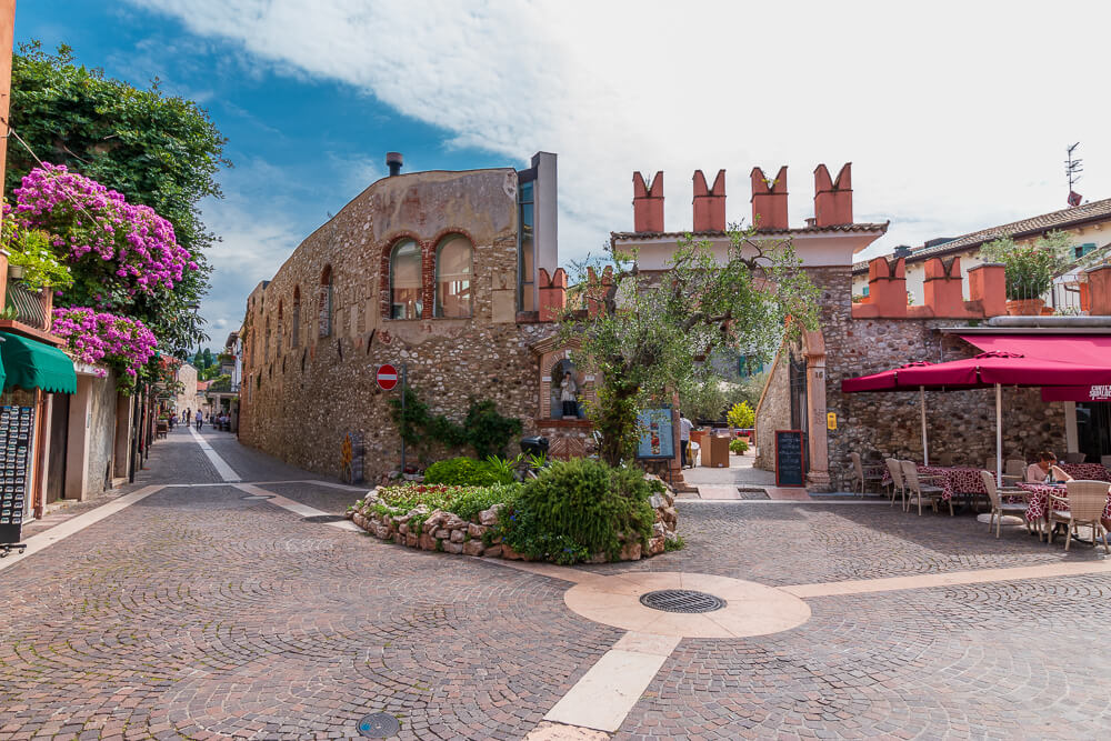 Blick auf alte Mauer in Bardolino am Gardasee hinter Restaurant mit roten Schirmen